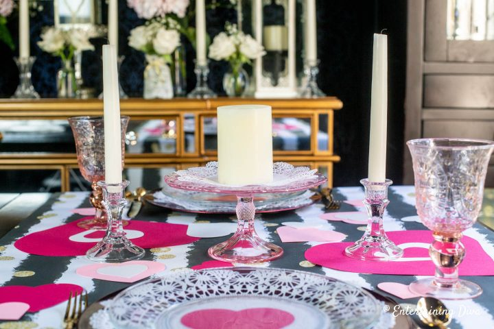 Valentine Day table centerpiece with pink glass cake stand, white candles and paper hearts