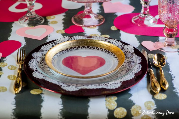 Valentine place setting with gold rimmed clear glass plate on a red charger plate