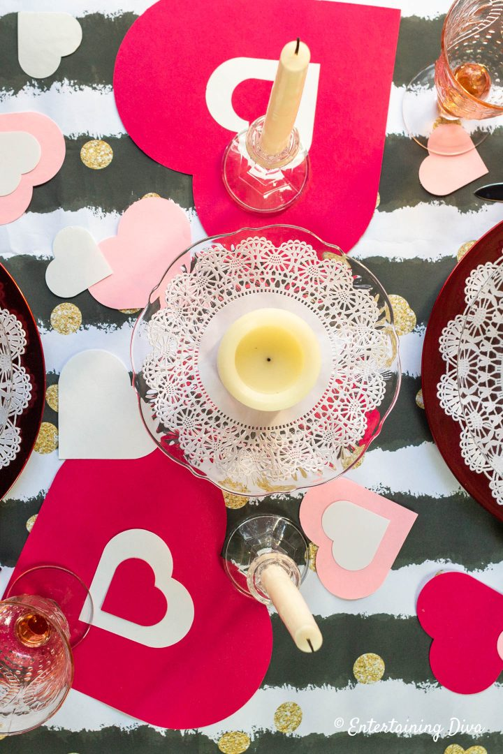 Red, white and pink hearts with white candles as a Valentine table centerpiece