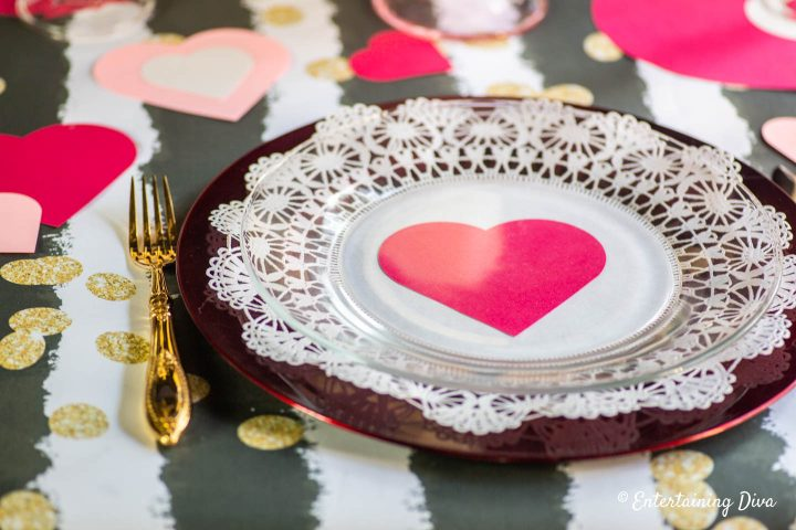 Red heart with white lace doily on a red charger as a Valentine table place setting