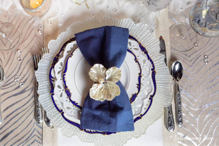 White, blue and gold table setting on winter wonderland tablescape