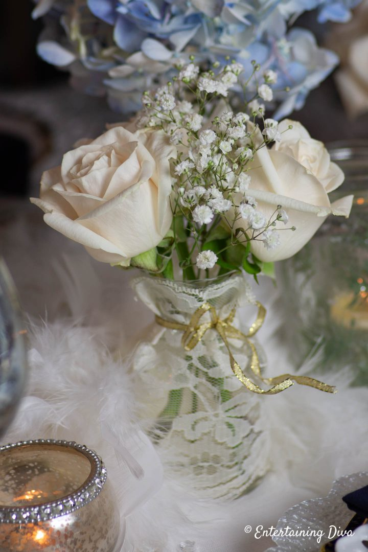 White roses and babies breath in a bud vase as part of a winter wonderland centerpiece