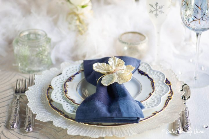 White glass charger, blue and gold-edge plates and blue napkins on a winter wonderland tablescape