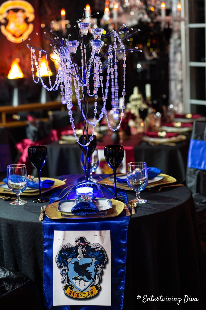 Ravenclaw table decor with a candle tree centerpiece uplit in blue