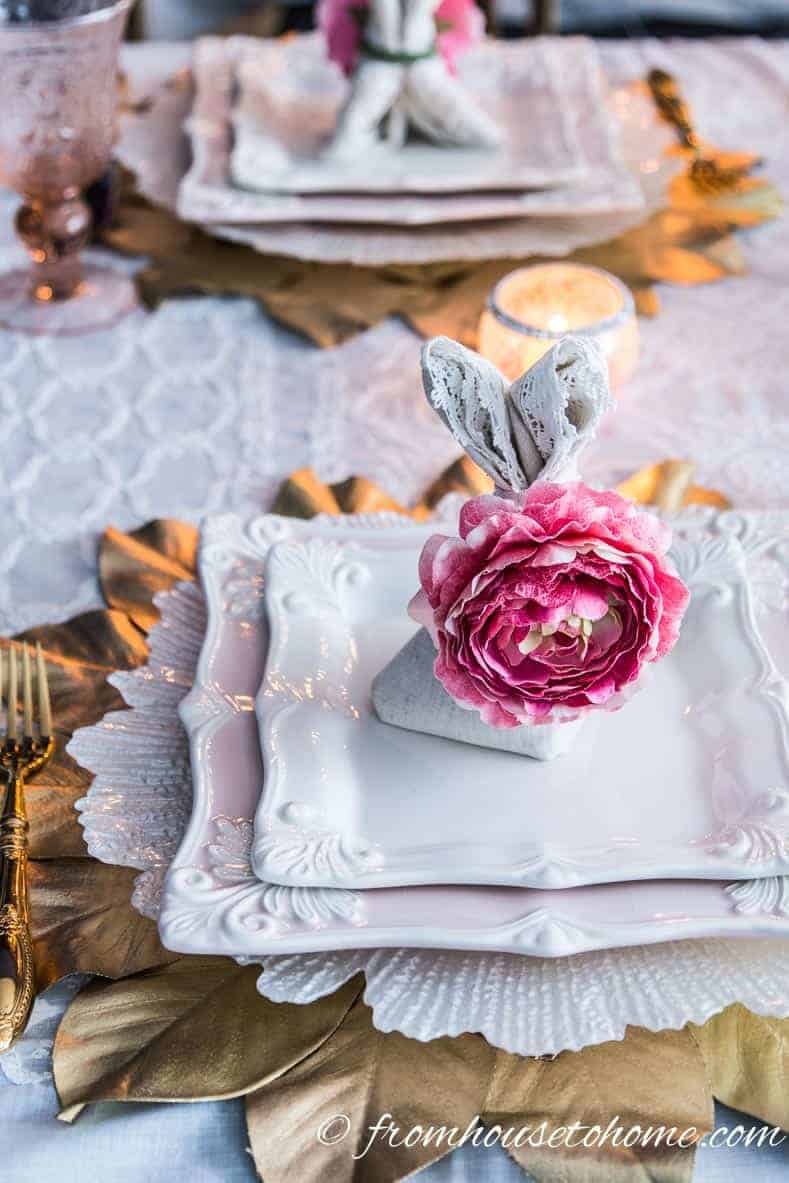 Pink, white and gold Easter table setting with bunny folded napkins