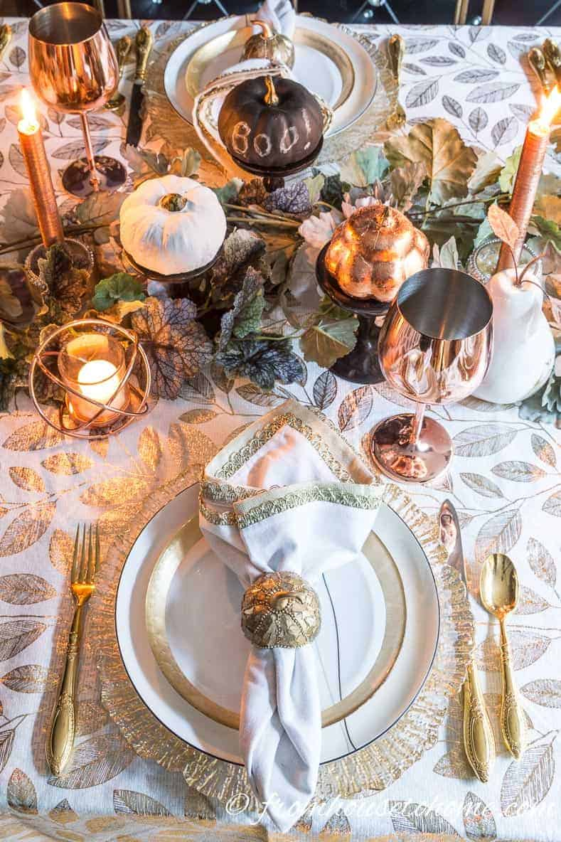 Gold and copper fall table setting with white and black mini pumpkins in the centerpiece