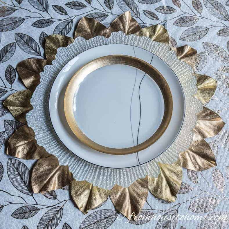 Gold, white and black place setting on a white and gold leaf tablecloth