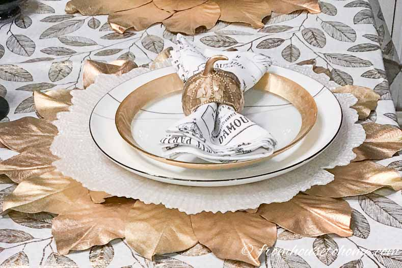 Copper pumpkin napkin holder on a white and gold table setting