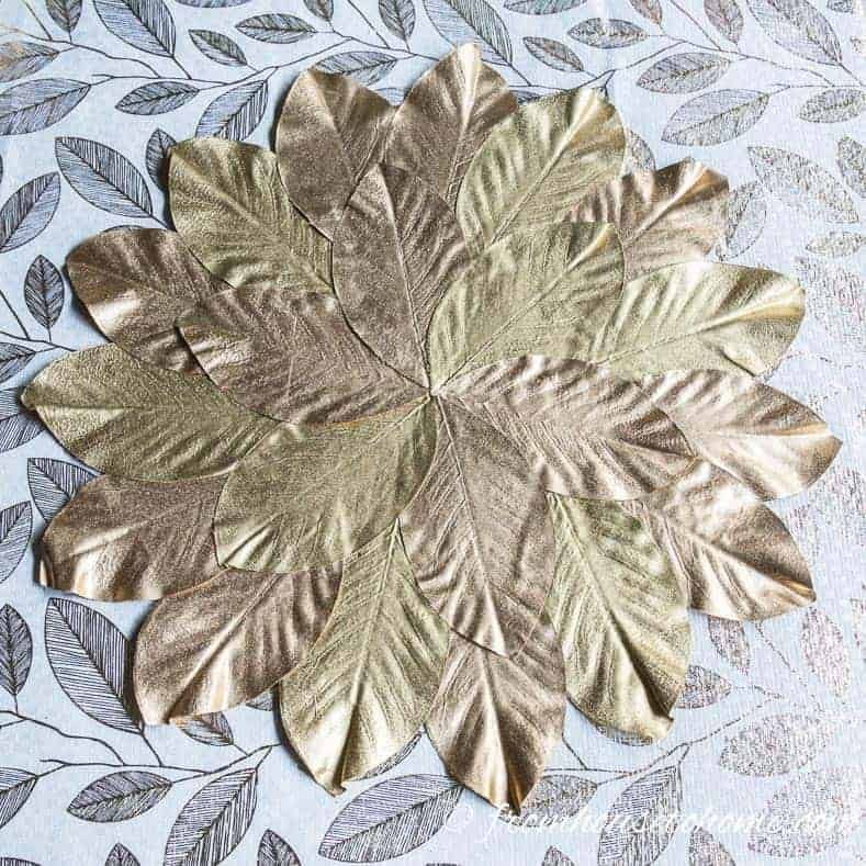 Gold magnolia leaf placemat on white and gold leaf tablecloth