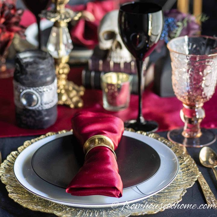 Halloween table setting with black plates, red table runner and gold charger