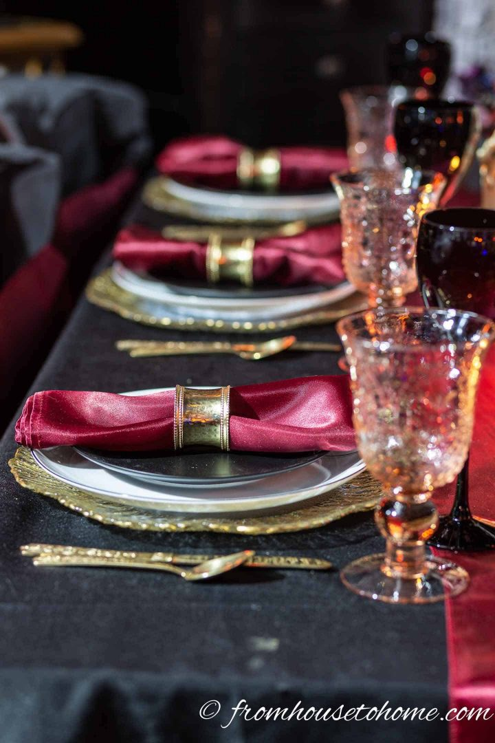 Black, gold and red table setting with pink water glasses and black wine glasses