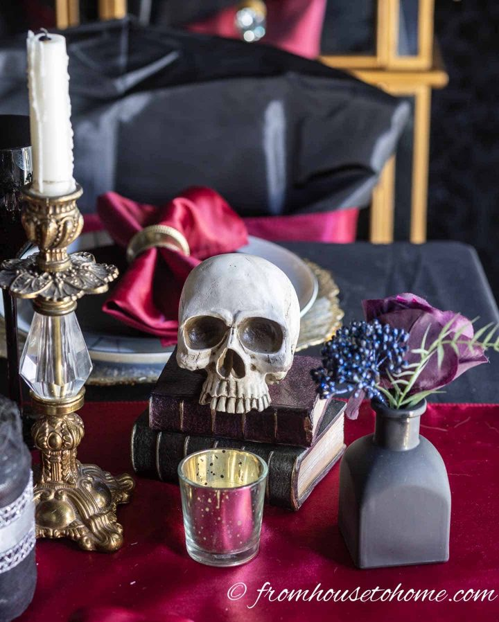Halloween centerpiece with a vintage gold candlestick, a skull on old books and a black vase
