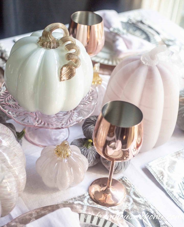 Pink and white glass pumpkins on cake stand