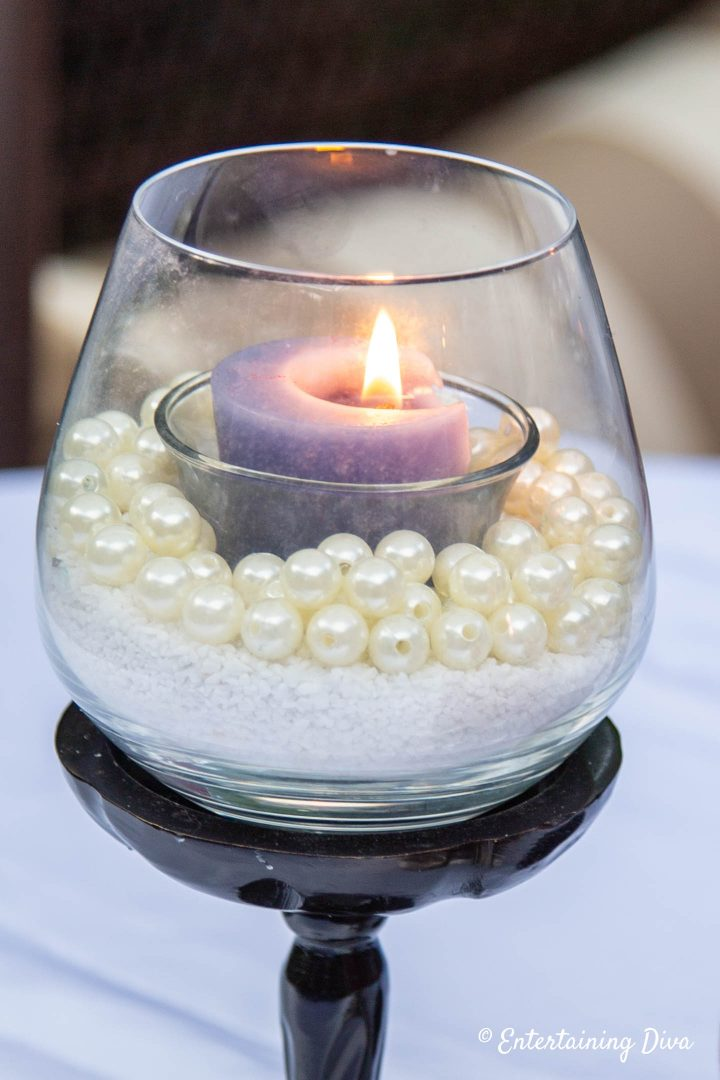 Stemless wine glass made into a candle holder with white sand, faux pearls and a blue votive candle