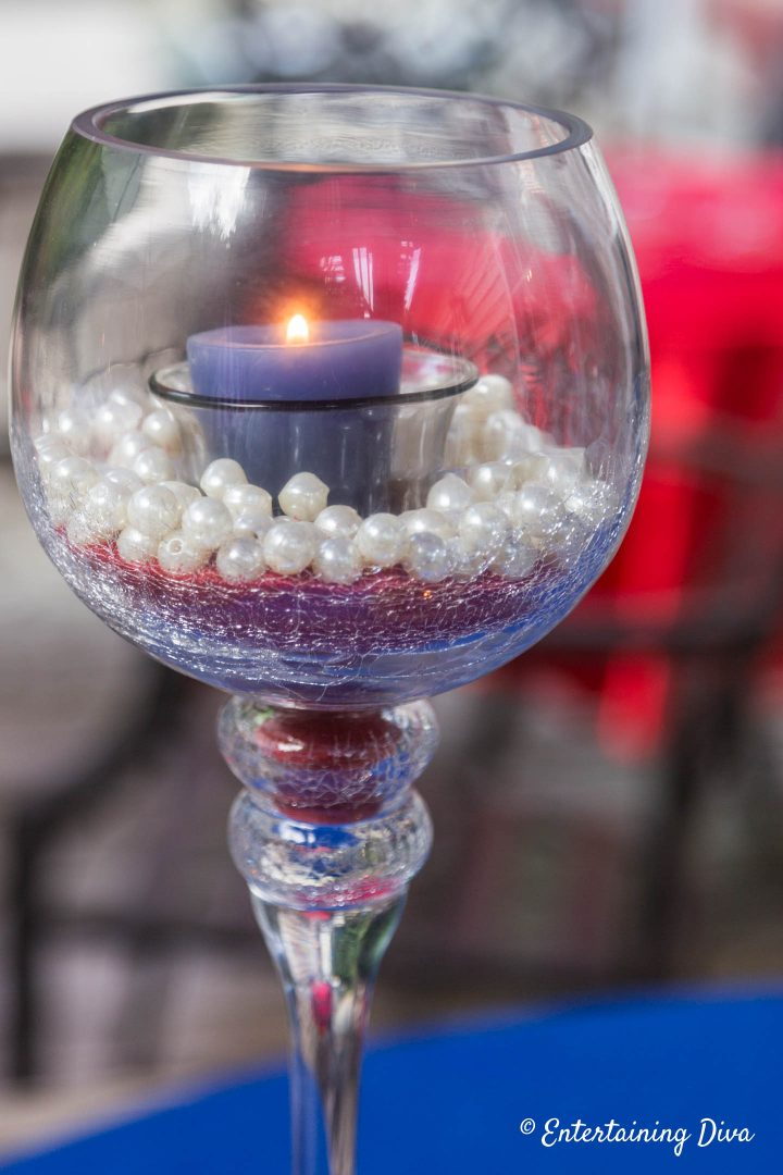 DIY pearl and sand candle holder made with red sand, white pearls and a blue candle