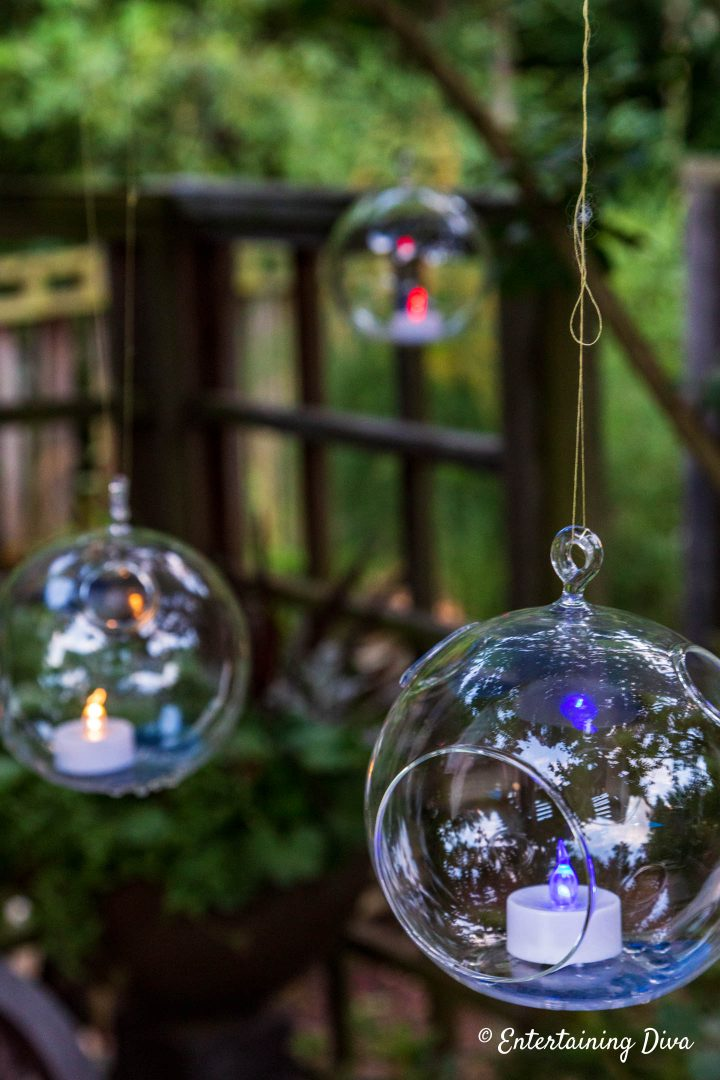 Red, white and blue flameless tealights in glass globe terrariums hung in the garden
