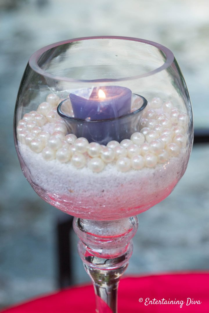 Blue candle in sand and faux pearls used as a centerpiece
