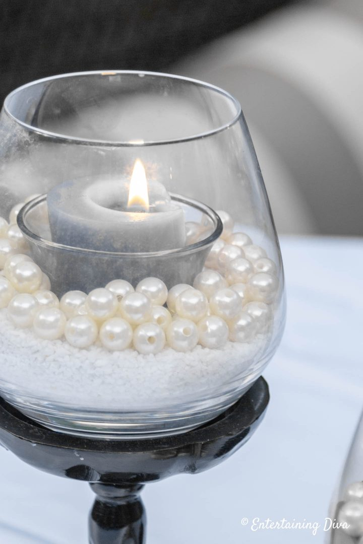 Grey votive candle in a sand and faux pearls candle holder