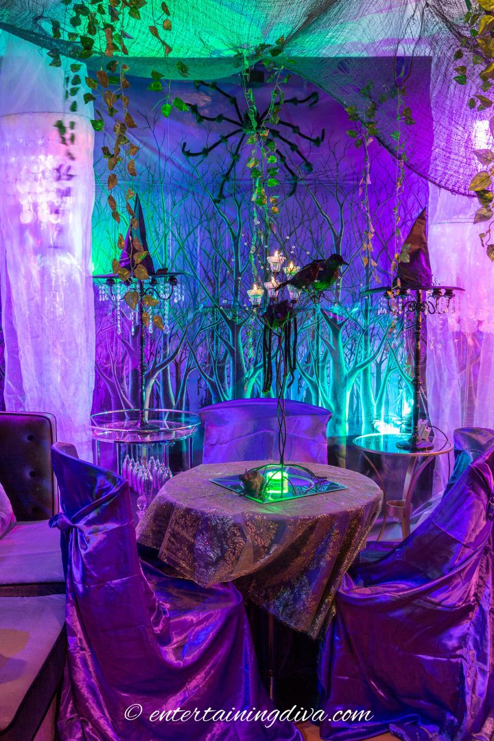 Maleficent party decor with a green lace overlays over a purple tablecloth