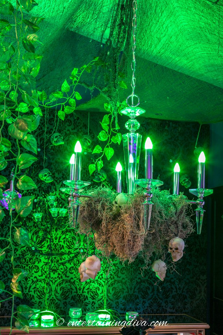 Maleficent party forest decor with green lights and Spanish moss draped on a chandelier
