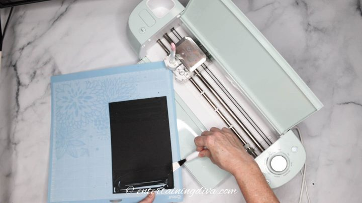 Removing paper from a Cricut mat using a Cricut weeding tool - the spatula