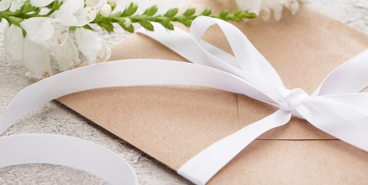 Invitation envelope wrapped in a bow