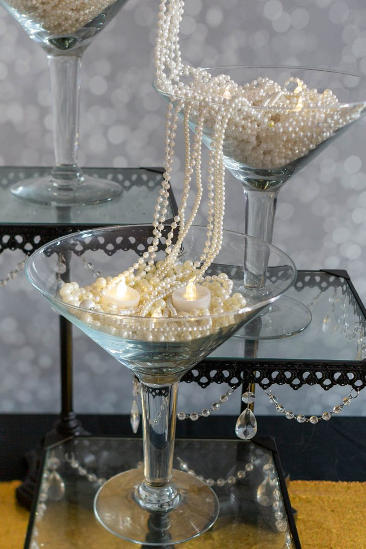 Centerpiece with strings of faux pearls streaming from one large martini glass to another