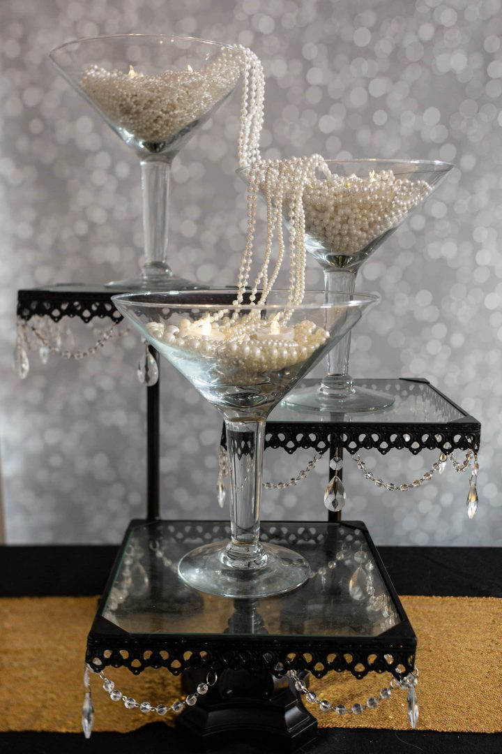 Great Gatsby centerpiece made with large martini glasses and strings of faux pearls