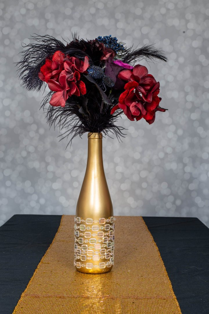 Embellished wine bottle centerpiece with faux flowers and black ostrich feathers