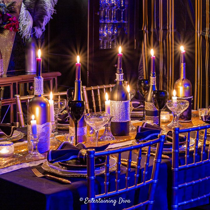 Great Gatsby party tablescape with embellished wine bottle candleholders as a centerpiece