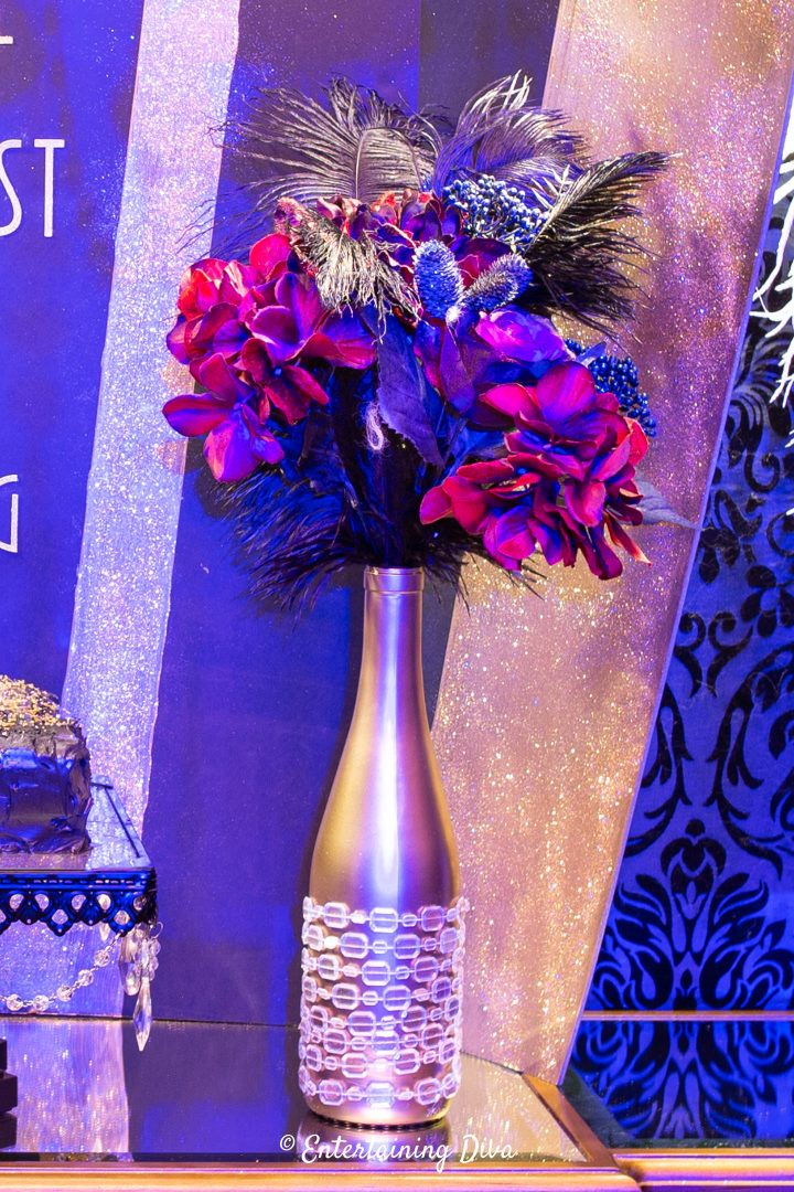 Great Gatsby centerpiece made with faux flowers, black ostrich feathers and an embellished wine bottle