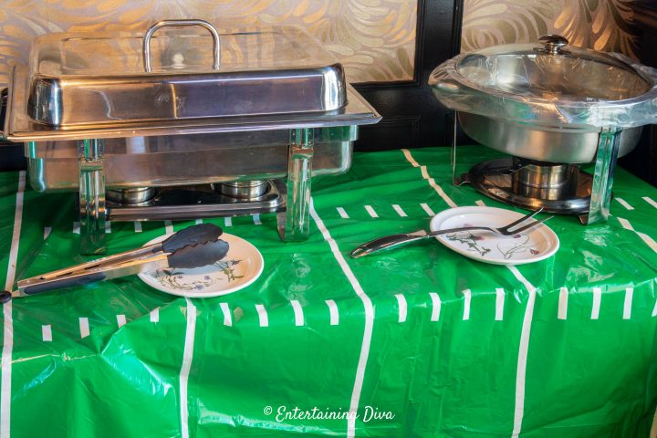 Serving utensils in front of chafing dishes on a buffet