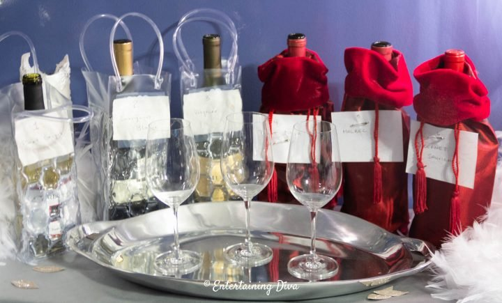 White and red wine bottles covered with wine bags for a blind wine tasting party