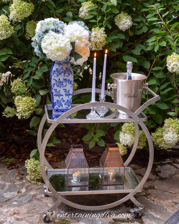 Bar cart with flowers, candles and champagne on a patio in front of a hydrangea