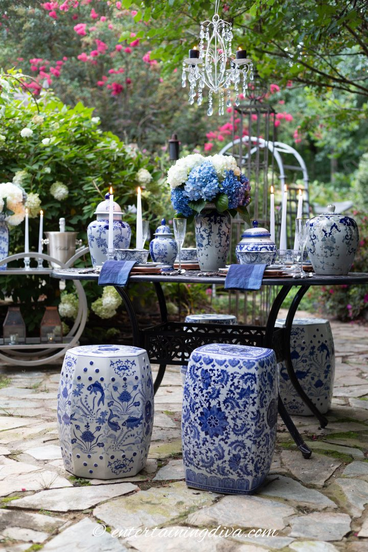 Blue and white outdoor tablescape with garden stools used as chairs