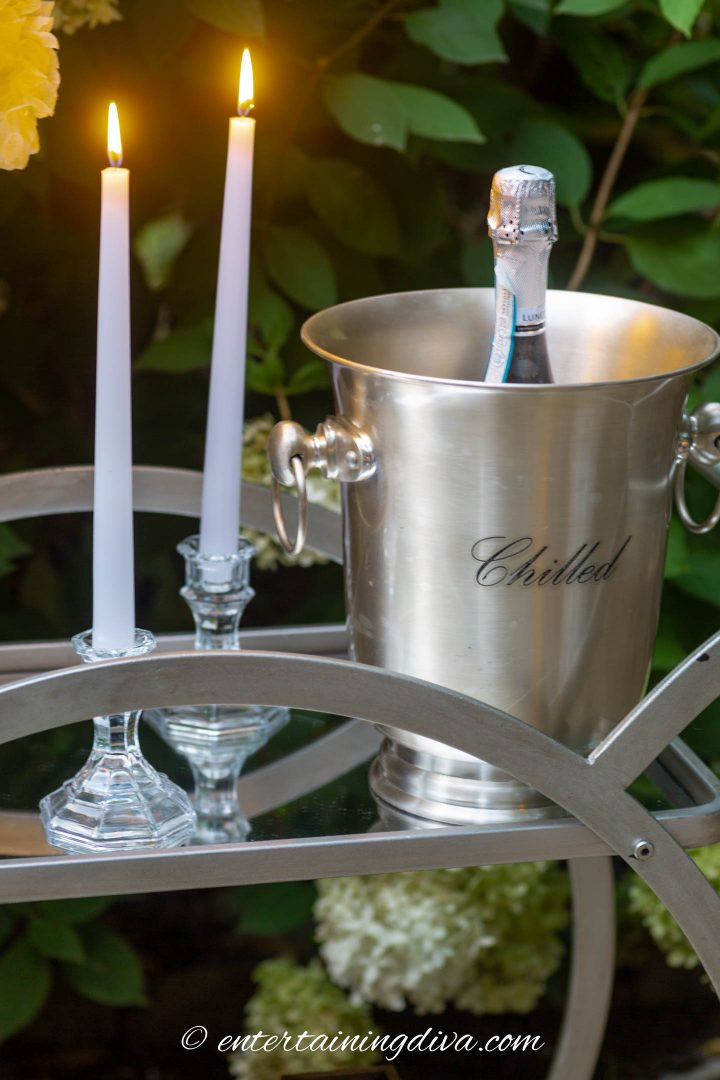 Candles and an ice bucket with champagne on a bar cart outside