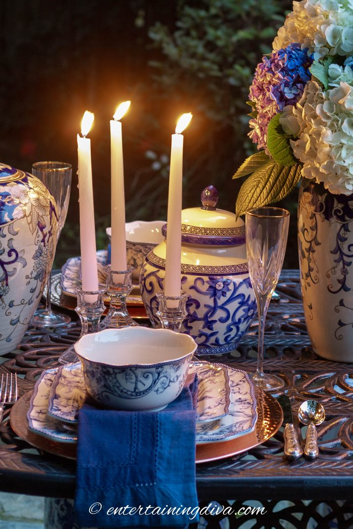 Blue and white ginger jars and candles used as a centerpiece on an outdoor table