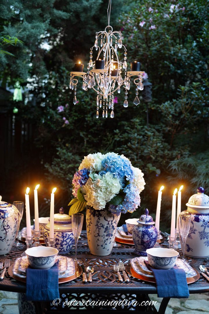 Blue and white outdoor tablescape with a candle chandelier hung above the table