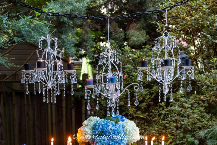 Three white candle chandeliers hung over an outdoor tablescape
