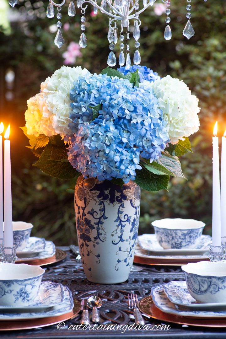 Blue and white ginger jar centerpiece with blue and white hydrangeas on an outdoor table