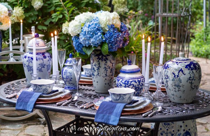 Blue and white outdoor dining table centerpiece made with ginger jars, flowers and candles