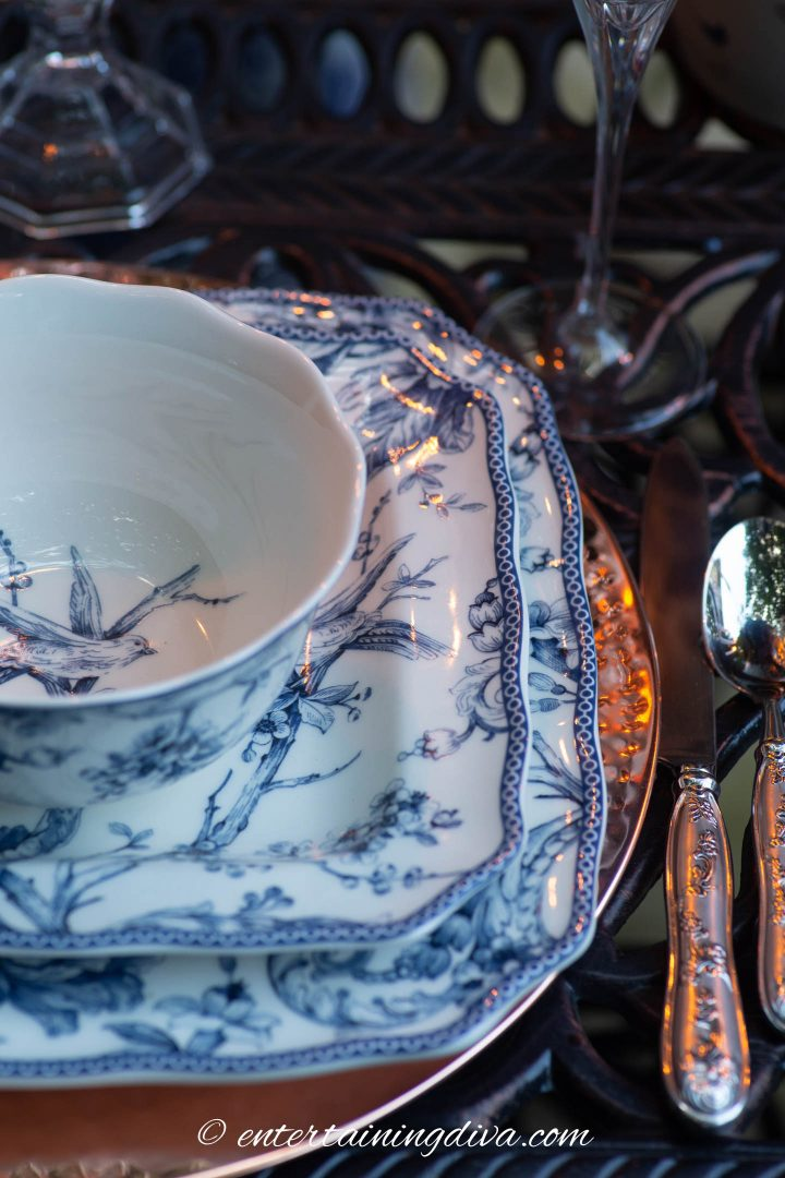 Blue and white dishes with a copper charger on an outdoor table