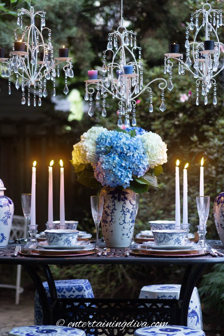 Three white candle chandeliers hung over a blue and white outdoor dinner party table setting