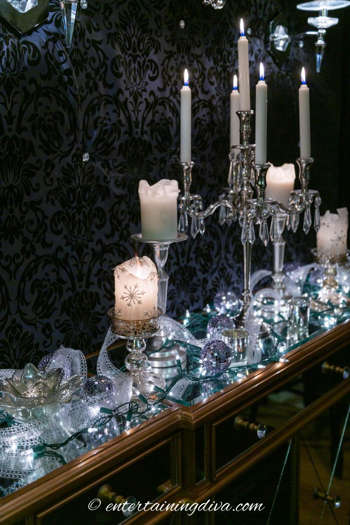 White Christmas lights, candles and silver ribbon on a buffet