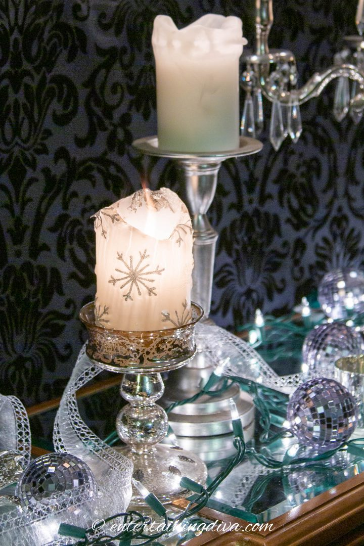 White candles, lights and ornaments used as Christmas decorations on a buffet