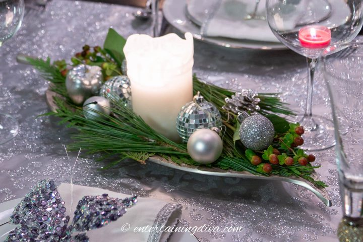 Christmas table centerpiece made from a tray filled with some evergreens, Christmas ornaments and a pillar candle