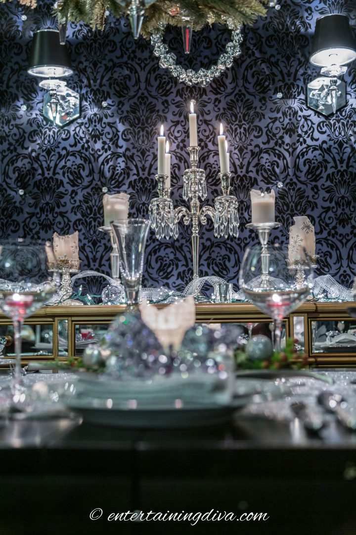 White candles with silver candle holders on a buffet