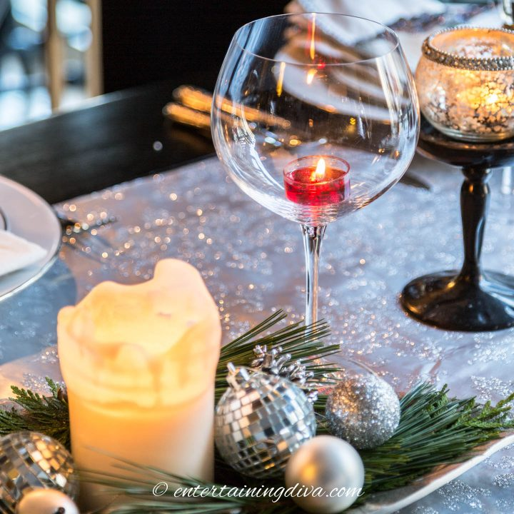 Christmas table with a wine glass used as a candle holder