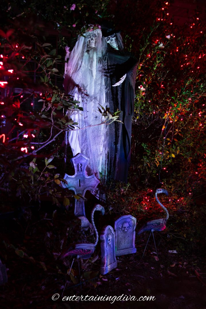 Bride and groom ghosts lit up at night in the Halloween cemetery