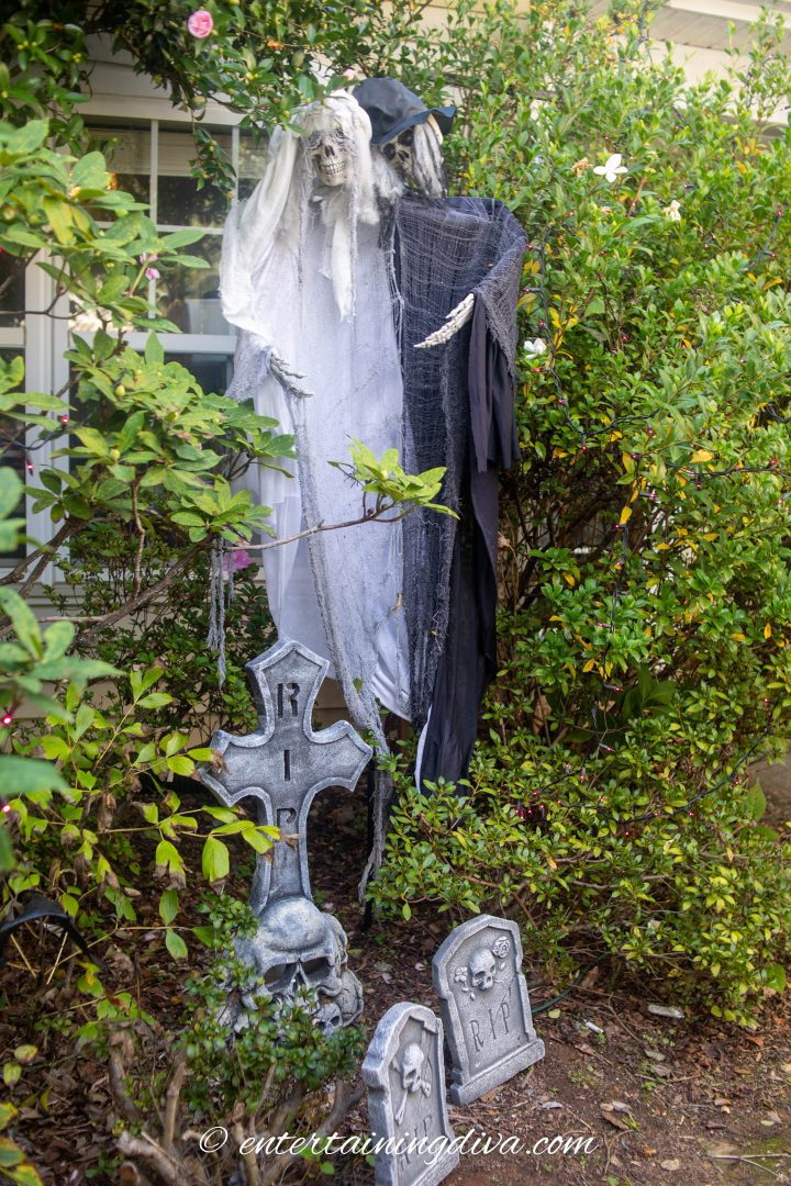 Bride and groom ghosts hidden in the bushes of a Halloween graveyard